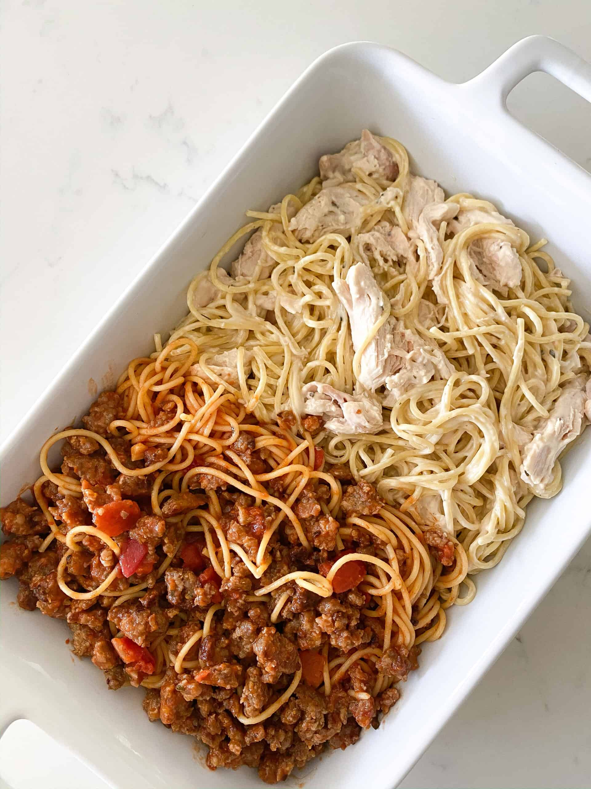 adding red sauce portion of baked spaghetti in baking dish