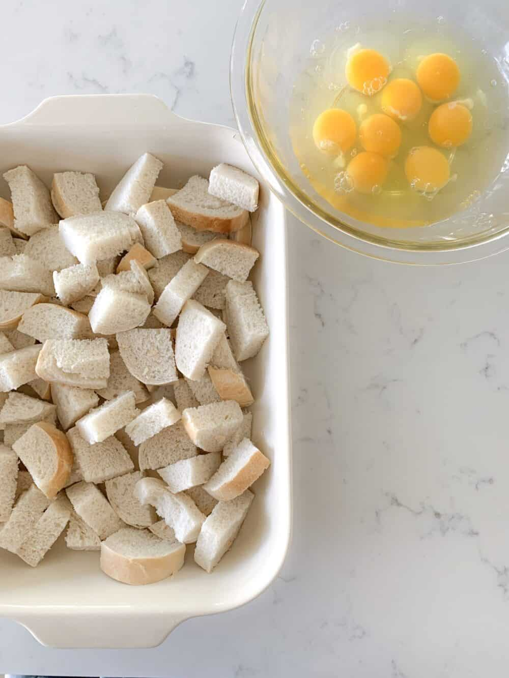 cubed bread in casserole dish and eggs in bowl