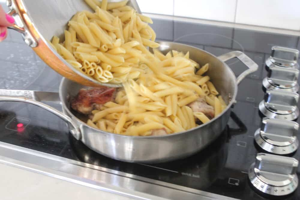 adding cooked penne to chicken in skillet