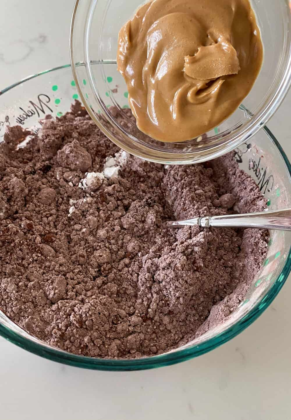 adding peanut butter to mixing bowl