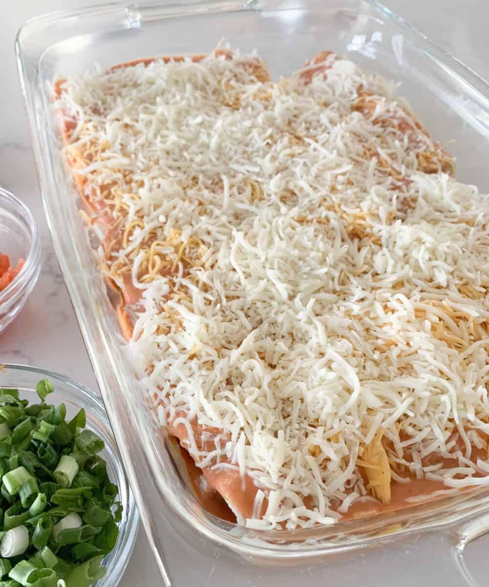 shredded cheese over pan of enchiladas