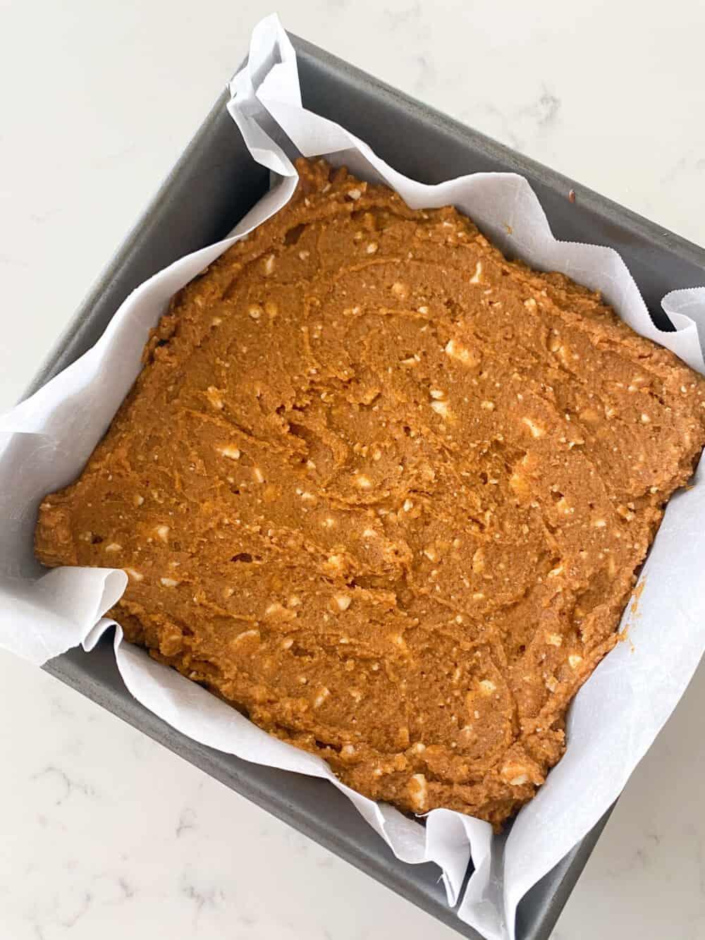 pumpkin blondies in baking dish ready to bake