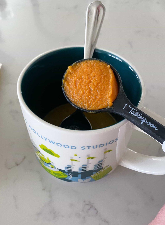 adding pumpkin to mug with