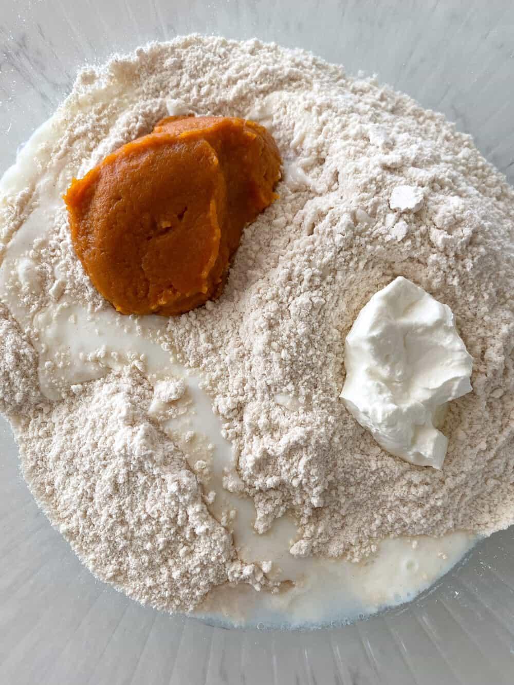pumpkin added to mixing bowl of pumpkin scones