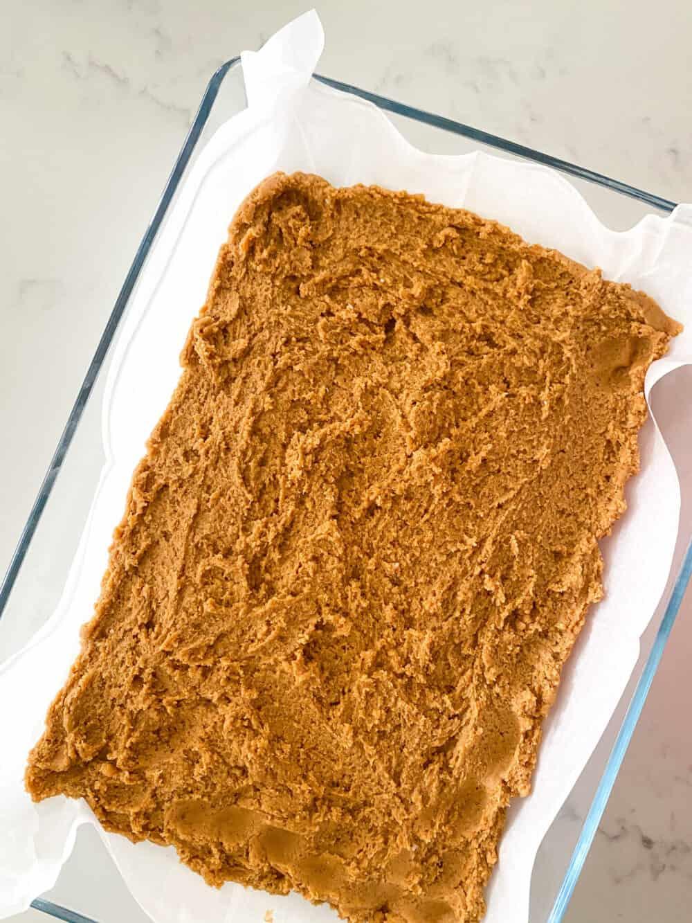pumpkin cheesecake bars dough inside baking dish
