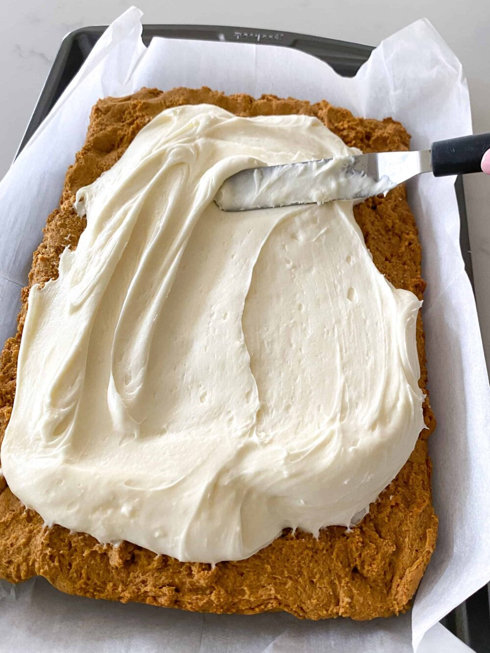 spreading cream cheese frosting over pumpkin cheesecake bars