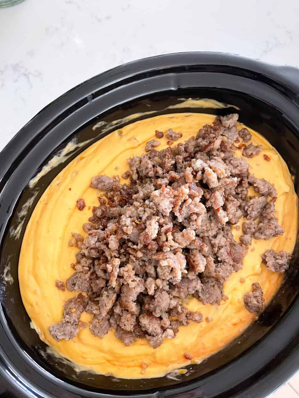 sausage added to cheese in crockpot for queso recipe