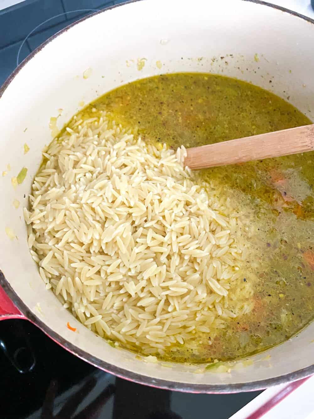 adding cooked orzo to soup pot