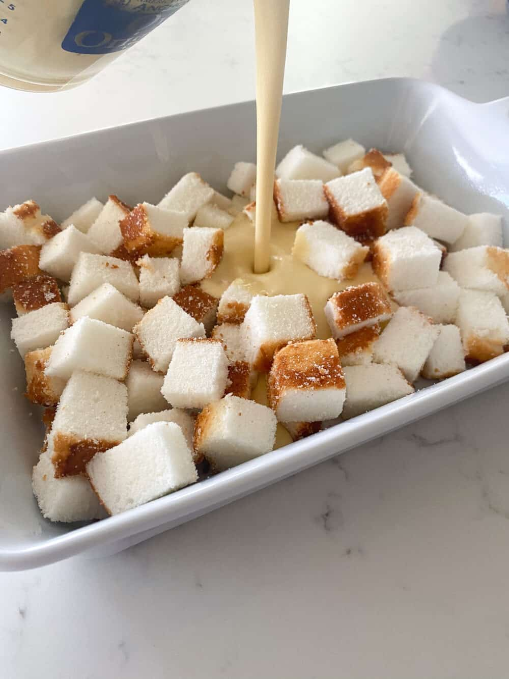 adding egg mixture to pound cake cubes in baking dish