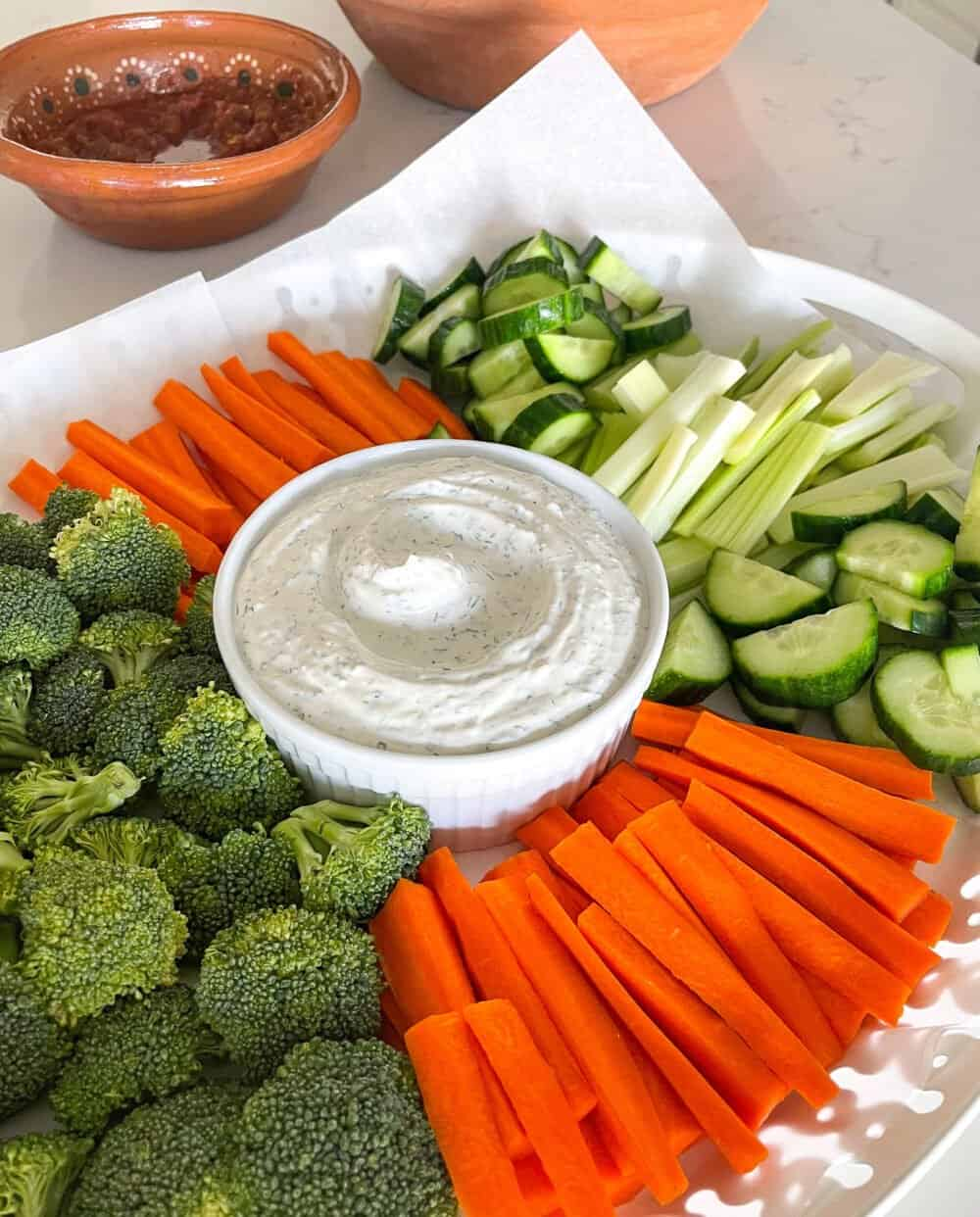 vegetables on serving tray with dip in middle